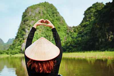 Buy stock photo Rearview shot of a young woman making a heart gesture while riding a boat down a river in Vietnam