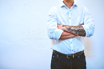 Buy stock photo Cropped shot of an unrecognizable businessman standing with his arms crossed in a modern office