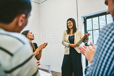 Buy stock photo Cropped shot of a diverse group of young businesspeople applauding their colleague during a seminar in a modern office