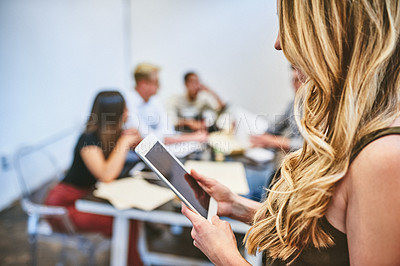 Buy stock photo Cropped shot of an unrecognizable businesswoman using a digital tablet in an office with her colleagues in the background