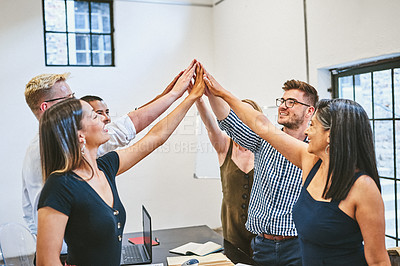 Buy stock photo Cropped shot of a diverse group of businesspeople joining their hands together in a huddle in a modern office