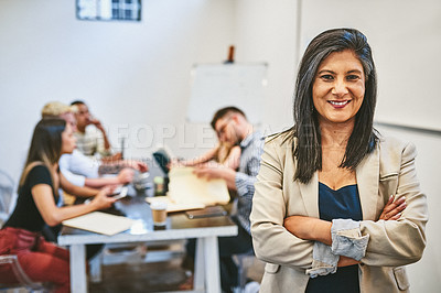 Buy stock photo Cropped portrait of an attractive middle aged businesswoman standing in an office with her colleagues in the background