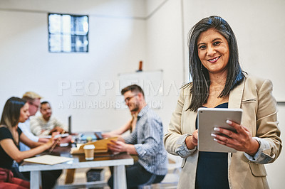 Buy stock photo Cropped portrait of an attractive middle aged businesswoman using a digital tablet in an office with her colleagues in the background