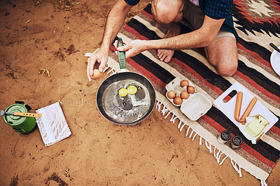 Buy stock photo Closeup shot of an unrecognisable man preparing food while camping in the wilderness