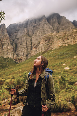 Buy stock photo Shot of a young woman hiking through the mountains