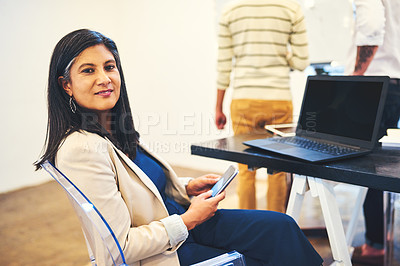 Buy stock photo Portrait of a mature businesswoman using a smartphone in a modern office
