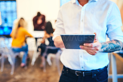 Buy stock photo Cropped shot of a businessman using a digital tablet with his team in the background of a modern office