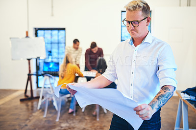 Buy stock photo Shot of a confident businessman designing a blueprint in a modern office with his team in the background