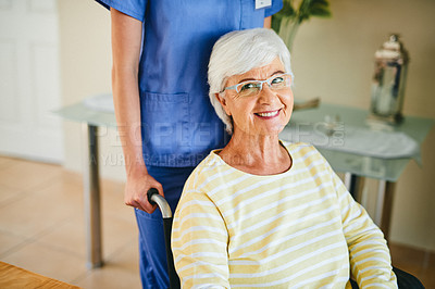 Buy stock photo Shot of a young nurse caring for a senior woman in a wheelchair