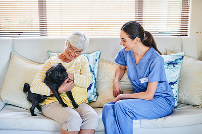 Buy stock photo Shot of a senior woman holding her dog while sitting with a female nurse