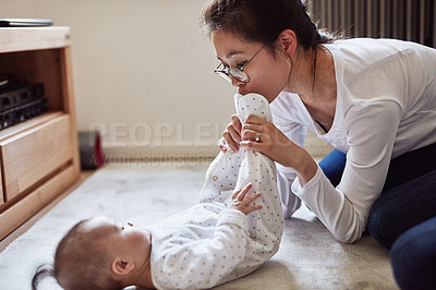 Buy stock photo Shot of a young woman spending quality time at home with her baby girl