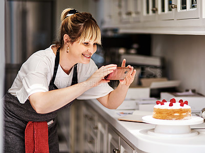 Buy stock photo Shot of a woman taking a picture of a cake she baked