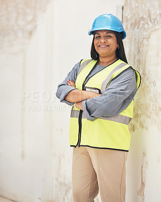 Buy stock photo Cropped portrait of an attractive young female construction worker standing with her arms folded on site