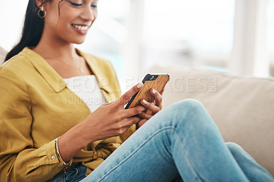 Buy stock photo Cropped shot of an attractive young businesswoman sitting on her couch and using her cellphone while at home