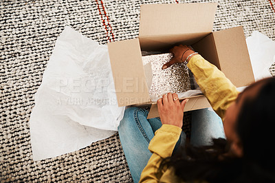 Buy stock photo High angle shot of an unrecognizable businesswoman sitting alone on her living room floor and opening up a mystery box