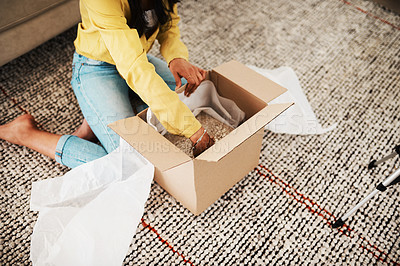 Buy stock photo Cropped shot of an unrecognizable businesswoman sitting alone on her living room floor and opening up a mystery box