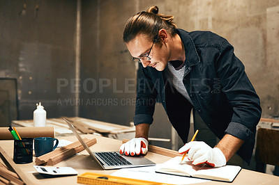 Buy stock photo Cropped shot of a focused young male carpenter working on a project inside of a workshop at night