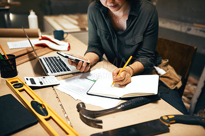 Buy stock photo Cropped shot of an attractive young female carpenter working on her laptop in the workshop