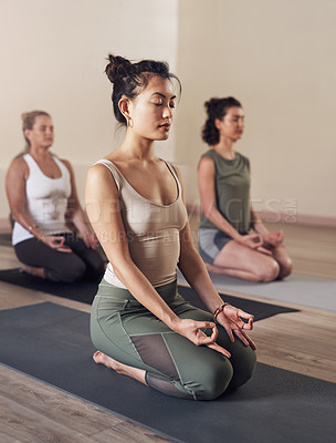 Buy stock photo Full length shot of a group of young people meditating and practicing yoga together inside a yoga studio