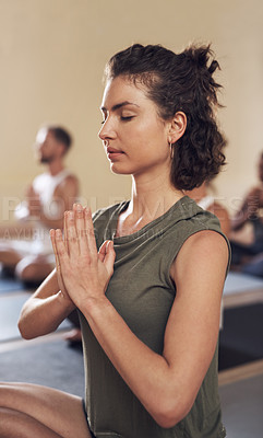 Buy stock photo Shot of an attractive young woman meditating in a yoga class