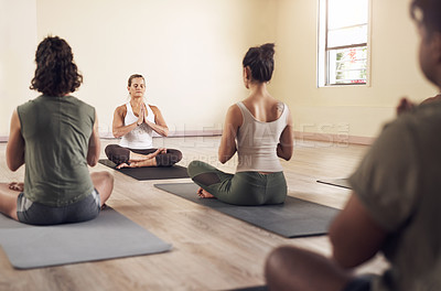 Buy stock photo Shot of a group of young people meditating and working out together in a yoga class