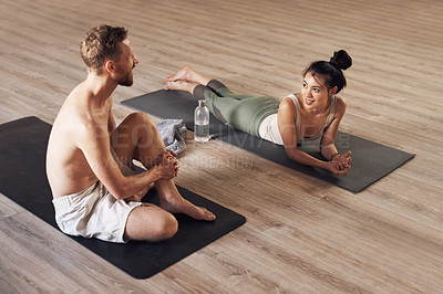 Buy stock photo Full length shot of two young people taking a break and chatting while working out together inside a yoga studio