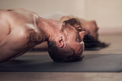 Buy stock photo Shot of a handsome young man working out and practicing yoga indoors