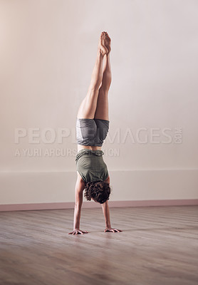 Buy stock photo Full length shot of an athletic young woman doing a hand stand in studio