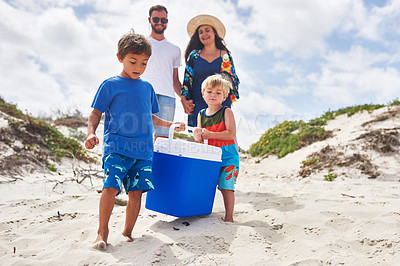 Buy stock photo Shot of two adorable little boys carrying a cooler box with their parents at the beach