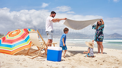 Buy stock photo Shot of a happy family spending some time together at the beach