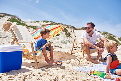 Buy stock photo Shot of a father and his two little sons enjoying a picnic at the beach