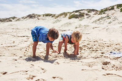 Buy stock photo Shot of two little boys playing in the sand at the beach