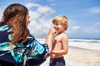 Buy stock photo Shot of a mother rubbing sunscreen lotion on her little son's face at the beach