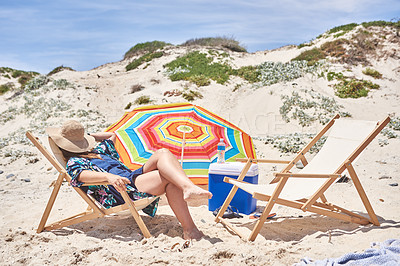 Buy stock photo Shot of a young woman relaxing on a deck chair at the beach