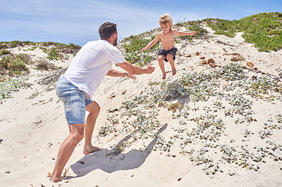 Buy stock photo Shot of a father playing with his little son at the beach