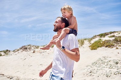 Buy stock photo Shot of a father carrying his little son on his shoulders at the beach