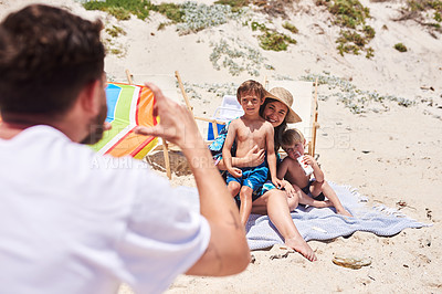 Buy stock photo Shot of a father taking a photo of his family at the beach