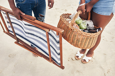 Buy stock photo Cropped shot of an unrecognizable couple carrying a beach chair and a picnic basket on the beach