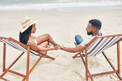 Buy stock photo Shot of a young couple relaxing on their chairs at the beach