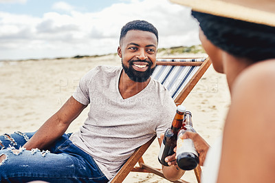 Buy stock photo Cropped shot of a couple relaxing on the beach with beers