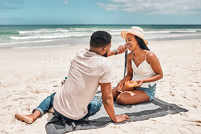 Buy stock photo Shot of a young couple having a picnic together at the beach