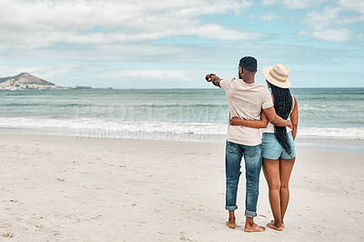 Buy stock photo Rearview shot of a young couple spending some time together at the beach