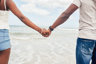 Buy stock photo Closeup shot of an unrecognisable couple holding hands at the beach