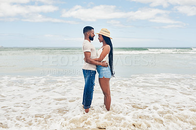 Buy stock photo Shot of an affectionate young couple standing face to face at the beach
