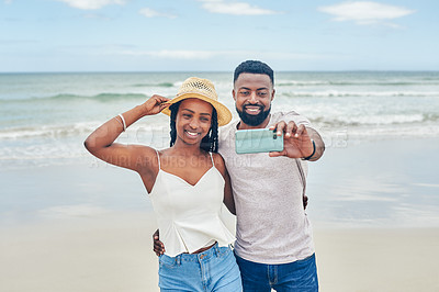 Buy stock photo Shot of a young couple taking selfies together at the beach