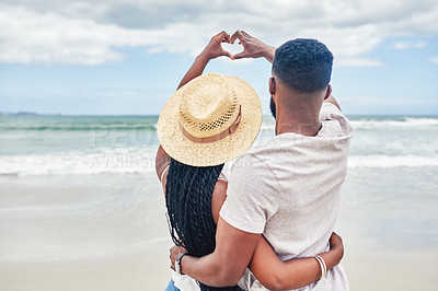 Buy stock photo Rearview shot of an affectionate young couple making a heart shape with their hands at the beach