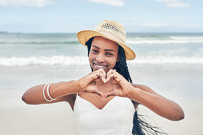 Buy stock photo Portrait of an attractive young woman making a heart shape with her hands at the beach