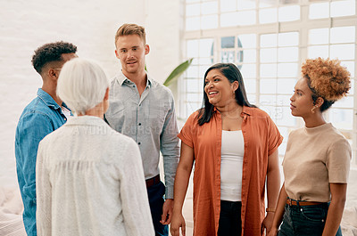 Buy stock photo Cropped shot of a diverse group of businesspeople standing together and having a discussion in the office