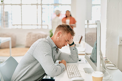 Buy stock photo Cropped shot of a handsome young businessman sitting and feeling stressed while using his computer in a coworking office space