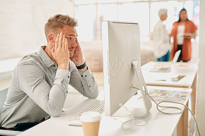 Buy stock photo Cropped shot of a handsome young businessman sitting and suffering from a headache in a coworking office space